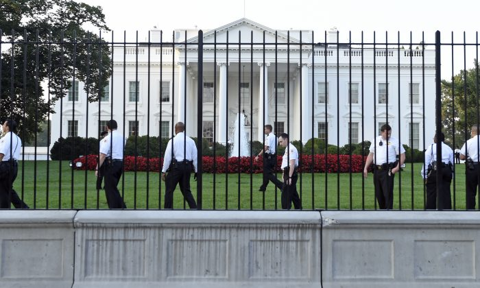 Uniformed Secret Service officers walk along the fence on the North side of the White House in Washington, Saturday, Sept. 20, 2014.   The Secret Service is coming under intense scrutiny after a man who hopped the White House fence made it all the way through the front door before being apprehended.  (AP Photo/Susan Walsh)