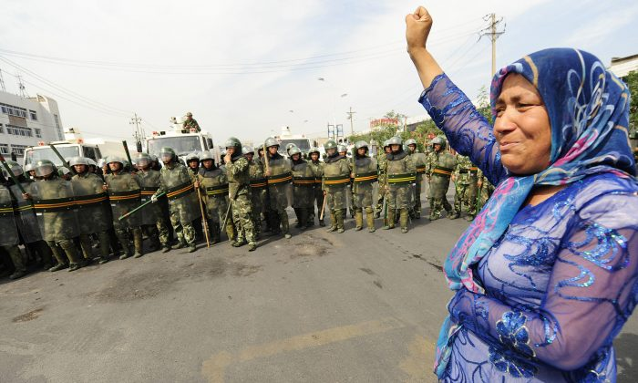 In this file photo, Chinese riot police watch a Muslim ethnic Uighur woman protest in Urumqi in China's far west Xinjiang province on July 7, 2009. (Peter Parks/AFP/Getty Images)