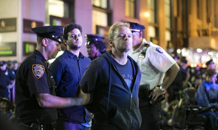 The NYPD arrests protesters during the Flood Wall Street protest at the intersection of Wall St. and Broadway in New York on Monday, Sept. 22, 2014. (Samira Bouaou/Epoch Times)