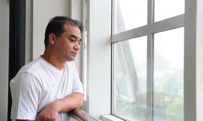 "University professor, blogger, and member of the Muslim Uighur minority, Ilham Tohti pauses for a few moments for a view from the window before a classroom lecture in Beijing on June 12, 2010. Tohti, considered ""China's Mandela,"" was recently sentenced to life in prison. (FREDERIC J. BROWN/AFP/Getty Images)"