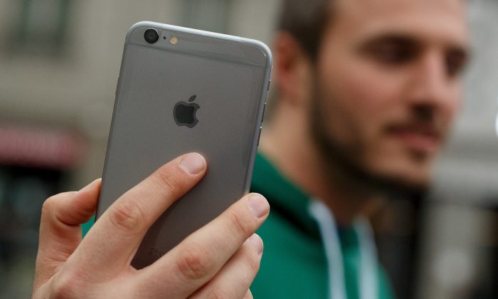 A man shows his new iPhone outside Puerta del Sol Apple Store as Apple launches iPhone 6 and iPhone 6 Plus on Sept. 26, 2014 in Madrid, Spain. (Pablo Blazquez Dominguez/Getty Images)