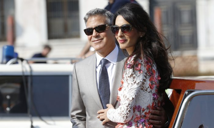 George Clooney is flanked by his wife Amal Alamuddin as they leave the Aman luxury Hotel in Venice, Italy, Sunday, Sept. 28, 2014. George Clooney married human rights lawyer Amal Alamuddin Saturday, the actor's representative said, out of sight of pursuing paparazzi and adoring crowds. (AP Photo/Luca Bruno)
