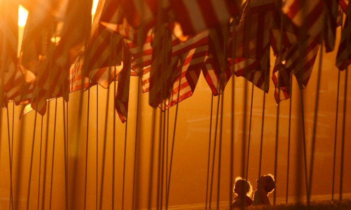 Children sit amongst U.S. national flags erected by students and staff from Pepperdine University to honour victims of the 9/11 attacks, in Malibu on Sept. 9, 2012. (Joe Klamar/AFP/GettyImages)