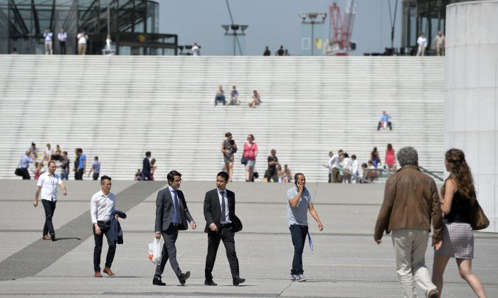People walk at La Defense business district, outsisde Paris, on July 17, 2014. 48% of the French people say they are pessimistic about their own future, even though their country has a good index of global development. (Miguel Medina/AFP/Getty Images)
