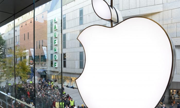 Customers queue to enter the Apple Store where a giant logo is displayed in the southern German city of Munich on Sept. 21, 2012 as the iPhone 5 goes on sale. (Christof Stache/AFP/Getty Images)