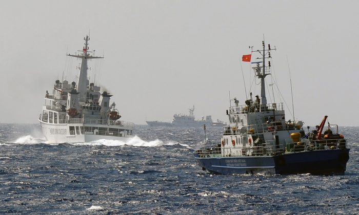 A China Coast Guard ship (L) blocks the way of a Vietnam Coast Guard ship near to the site of a Chinese drilling oil rig (R, background) being installed in the disputed waters in the South China Sea off Vietnam's central coast on May 14, 2014. (Hoang Dinh Nam/AFP/Getty Images)