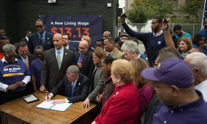 New York City Mayor Bill de Blasio signs an executive order to raise the living wage for workers employed at city-subsidized developments, at St. Mary's Park in the Bronx, N.Y., on Sept. 30, 2014. Workers will now earn $13.13 an hour, and retail tenants at the developments will also be required to pay the higher rate. (The New York City Mayor's Office)