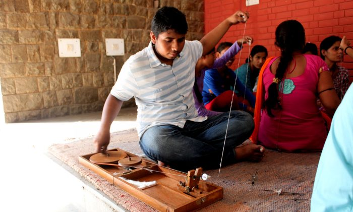 A student works on his charkha at the Gandhi Bhavan Center of Delhi University on Sept. 18, 2014. The course is helping to revive Gandhian value and teach Indian youth how to be self-reliant. (Venus Upadhayaya/Epoch Times)