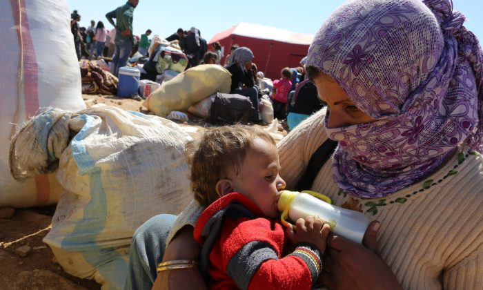 A mother feeds her baby as thousands of new Syrian refugees from Kobani arrive at the Turkey-Syria border  crossing of Yumurtalik near Suruc, Turkey, Wednesday, Oct. 1, 2014. (AP Photo/Burhan Ozbilici)