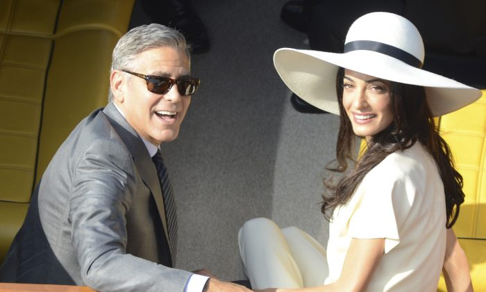 George Clooney and his wife Amal Alamuddin leave the city hall after their civil marriage ceremony in Venice, Italy on Sept. 29, 2014. (AP Photo/Luigi Costantini)