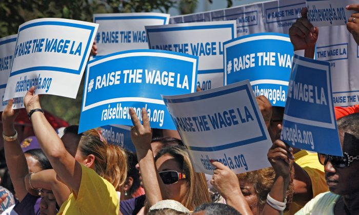 Supporters carry signs to raise the minimum wage in Los Angeles as they listen to Mayor Eric Garcetti during an announcement at the Martin Luther King Jr. Park with a coalition of business, labor, community, and faith leaders from across the city on Sept. 1, 2014. Garcetti announced his proposal to raise the minimum wage in Los Angeles from the current $9 an hour to $15 in 2020. (Richard Vogel/AP)