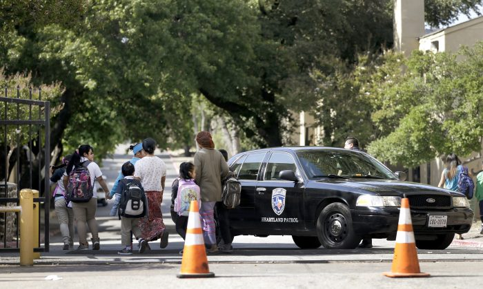 Families walk by a law enforcement vehicle near the main entrance to The Ivy Apartments as children return from school, Wednesday, Oct. 1, 2014, in Dallas. The man diagnosed with having the Ebola virus was staying at the complex with family and is now hospitalized. (AP Photo/Tony Gutierrez)