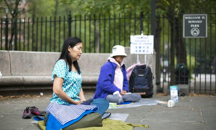 Practitioners of Falun Dafa meditate in the William H. Seward park in Chinatown, Manhattan, on Sept. 29, 2014. (Samira Bouaou/Epoch Times)