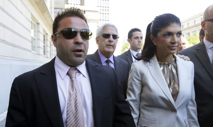 """FILE - In this July 30, 2013 file photo, """"The Real Housewives of New Jersey"""" stars Giuseppe """"Joe"""" Giudice, 43, left, and his wife, Teresa Giudice, 41, of Montville Township, N.J., walk out of Martin Luther King, Jr. Courthouse after an appearance in Newark, N.J. Teresa and Giuseppe """"Joe"""" Giudice are scheduled to be sentenced Thursday Oct. 2, 2014 on conspiracy and bankruptcy fraud charges in federal court in Newark.  (AP Photo/Julio Cortez, File)"""