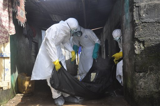 Health workers in protective gear remove the body of a woman suspected to have died from the Ebola virus, near the area of Freeport in Monrovia, Liberia. (AP Photo/Abbas Dulleh)