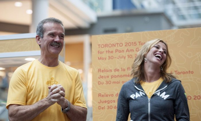 Chris Hadfield and former Olympian Catriona Le May Doan laugh during the announcement of the route for the Toronto 2015 Pan Am Torch Relay at the Eaton Centre in Toronto on Oct. 1, 2014. (The Canadian Press/Hannah Yoon)