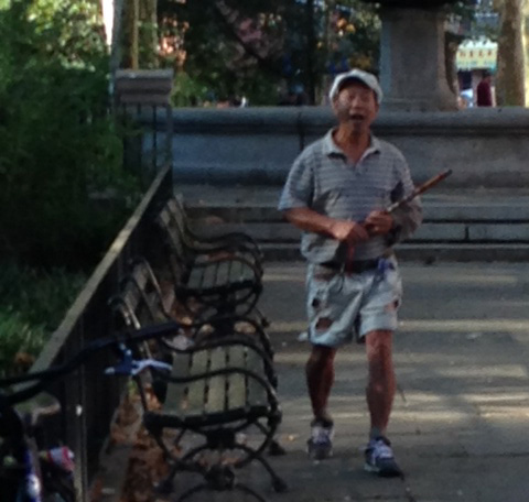 One of the alleged harassers of Falun Gong practitioners, taken in Manhattan, N.Y., September 2014, moments before he began to physically and verbally threaten the practitioners. The man swung his bamboo flute at one practitioner. (Lily Hung)
