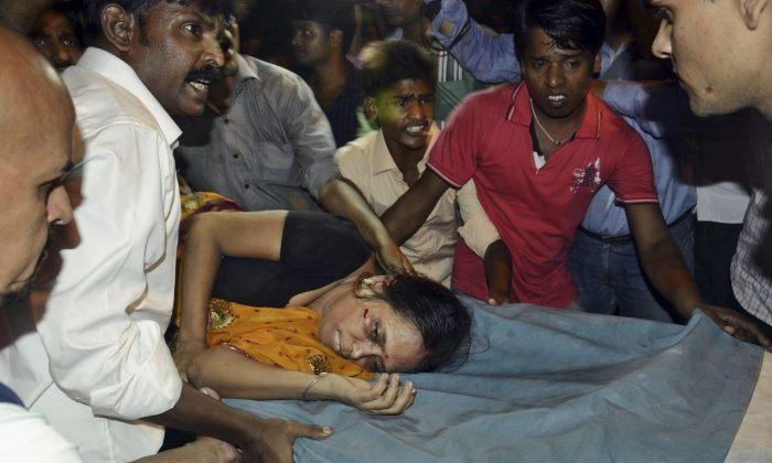 An Injured woman is carried on a stretcher to a hospital for treatment in Patna, India, Friday, Oct. 3, 2014. (AP Photo/Aftab Alam Siddiqui)