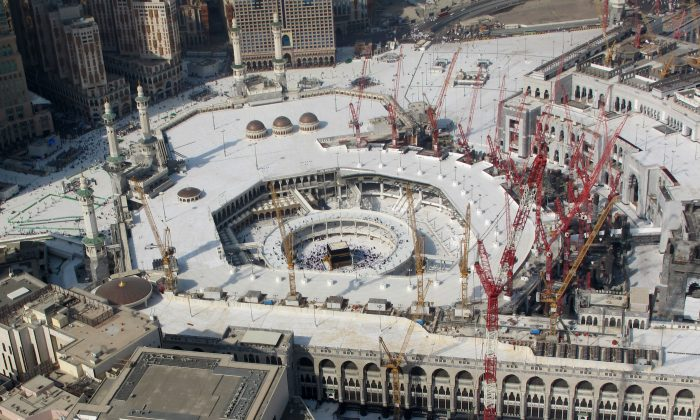 This aerial image made from a helicopter shows Muslim pilgrims circling the the Kaaba in the Grand Mosque in the Muslim holy city of Mecca, Saudi Arabia, during the annual pilgrimage, known as the hajj, near Mecca, Saudi Arabia, Friday, Oct. 3, 2014. (AP Photo/Benjamin Wiacek)