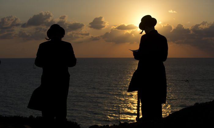 """Ultra-Orthodox Jews of the Hassidic sect Vizhnitz gather on a hill overlooking the Mediterranean sea as they participate in a ceremony in Herzeliya, Israel, Thursday, Oct. 2, 2014. Tashlich, which means """"to cast away"""" in Hebrew, is the practice by which Jews go to a large flowing body of water and symbolically """"throw away"""" their sins by throwing a piece of bread, or similar food, into the water before the Jewish holiday of Yom Kippur, which start on Friday. (AP Photo/Oded Balilty)"""