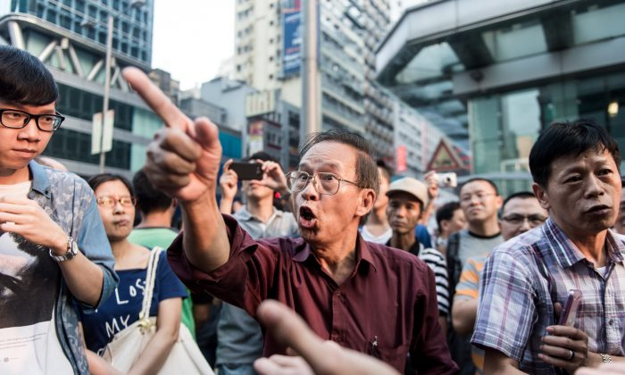 A man (C) gestures as he calls for pro-democracy protesters to leave the Mong Kok District of Hong Kong on Oct. 5. On Oct. 2, 142 oversea Chinese language media under the Chinese International Media Association published a pro-Chinese Communist Party statement condemning Occupy Central as illegal. (Anthony Wallace/AFP/Getty Images)