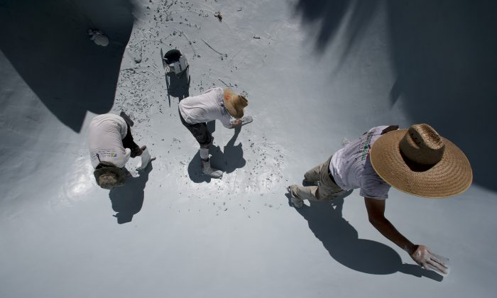 Workers replace the plaster in a swimming pool in Santa Ana, Calif. on Wednesday, Sept. 24, 2014. California swimming pool companies just regaining their financial footing after the recession are now facing a new challenge: a devastating drought that has put the state's ubiquitous backyard pools under the microscope. (AP Photo/Chris Carlson)