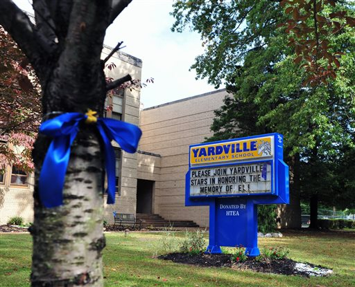 A blue and gold ribbon wrap around a tree in front of Yardville Elementary School in Hamilton Township, N.J., Saturday, Oct. 4, 2014. The ribbon and sign honored the memory of a preschooler who died on Sept. 25 of enterovirus 68. (AP Photo/The Trentonian, Scott Ketterer)