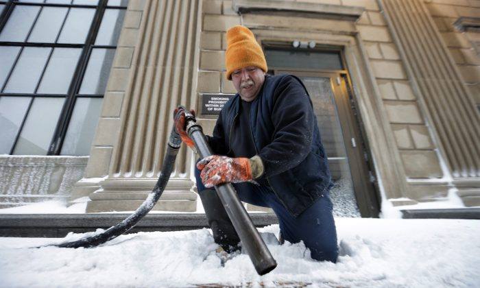 FILE - In this Feb. 13, 2014 file photo, John Wood, of Bordentown, N.J., delivers heating oil in Trenton, N.J. The Energy Department's annual prediction of winter heating costs released Tuesday, Oct. 7, 2014 says that Americans will pay less because they won't have to crank up the heat as much. (AP Photo/Mel Evans, File)