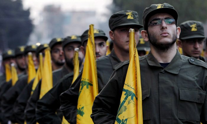 Hezbollah fighters hold their party flags, on Nov. 12, 2010, as they parade during the opening of new cemetery for colleagues who died in fighting against Israel, in a southern suburb of Beirut, Lebanon. (AP Photo/Hussein Malla)