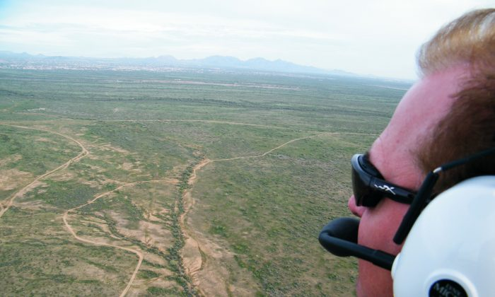 This March 12, 2009 photo provided by Arizona Powerchutes shows instructor Randy Long flying over the Sonoran Desert while powerchuting, in Phoenix, Ariz. Picture a dune buggy with a massive parachute attached to the back of it, sort of a cross between something the Wright Brothers might have designed and that flying machine from the Mad Max movies. Powerchuting provides a flying experience unlike any other. (AP Photo/Arizona Powerchutes)