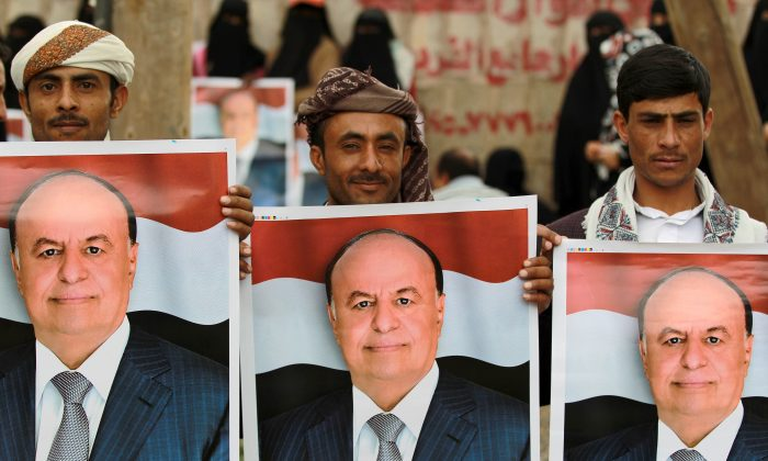 Demonstrators hold up posters bearing the portrait of Yemen's President Abd-Rabbu Mansour Hadi during a pro-government demonstration on Aug. 26, 2014, in the Yemeni capital Sanaa. Rival protests stoked up tension in Yemeni capital Sanaa on Aug. 24, as a presidential negotiating team abandoned talks with Shiite rebels, accusing them of seeking to ignite a war. (Mohamed Huwais/AFP/Getty Images)