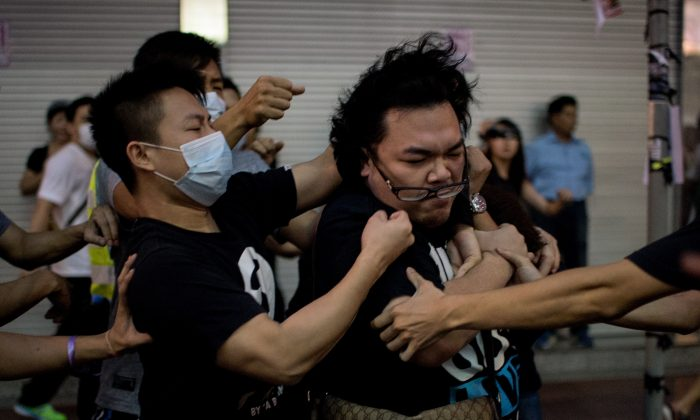 A group of men in masks beat up a man (R) who tried to stop them from removing barricades from a pro-democracy protest area in the Causeway Bay district of Hong Kong on Oct. 3, 2014. Sources say Hong Kong's chief executive Leung Chun-ying has employed mafia groups to harass the protesters. (Alex Ogle/AFP/Getty Images)