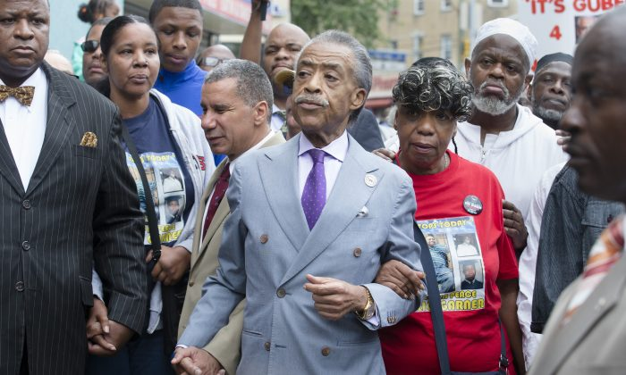 The Rev. Al Sharpton (C) holds hands with former New York Gov. David Paterson (L) and Gwen Carr (R), mother of Eric Garner, as they arrive before a march to protest the death of 43-year-old Eric Garner in the Staten Island borough of New York on Aug. 23, 2014. The Garner family has filed a notice of claim to sue New York City, the Police Department, and six individual police officers for $75 million. (AP Photo/John Minchillo)