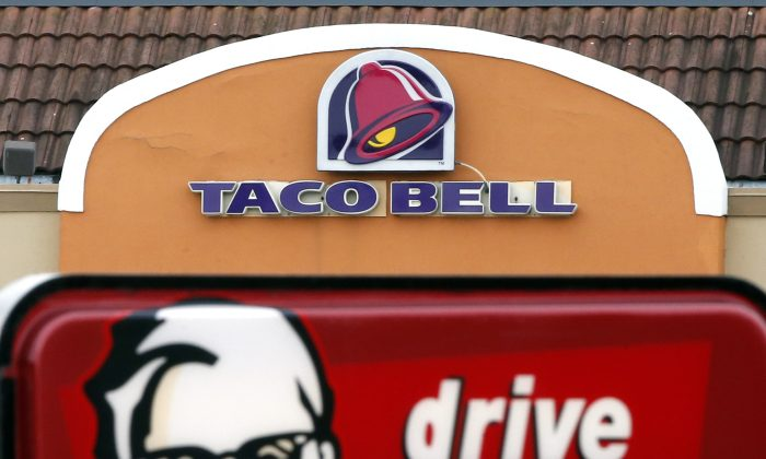 A Taco Bell facade behind a KFC drive-thru sign in Saugus, Mass., on Jan. 31, 2014. (Elise Amendola/File Photo via AP)