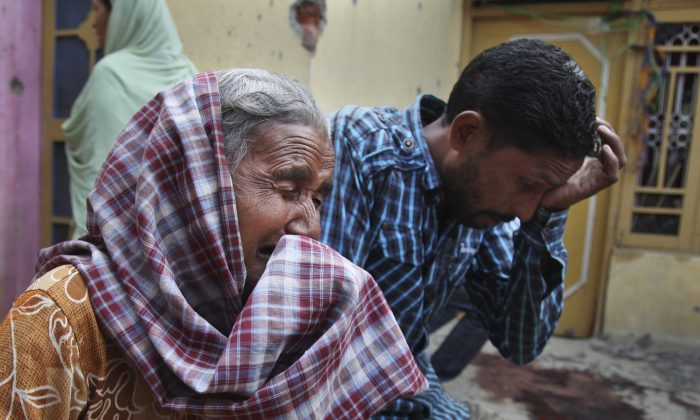 Relatives of Rajesh Kumar, who was killed in mortar shell firing allegedly from the Pakistan's side, weep inside their residential house at Masha da kothe village, in Arnia Sector near the India-Pakistan international border, about 47 kilometers (30 miles) from Jammu, India, Monday, Oct. 6, 2014. Tens of thousands of villagers were fleeing their homes in Kashmir on Monday, as Indian and Pakistani troops bombarded each another with gunfire and mortar shells over the border separating Pakistan from India's portion of the disputed region. At least nine civilians were killed. (AP Photo/Channi Anand)