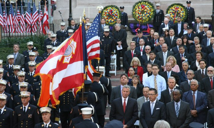 Firefighters bring the flags up as New York City mayor Bill de Blasio (front, L) looks on, at the Firemen's Monument in Manhattan, N.Y., on Oct. 8, 2014. (Shannon Liao/Epoch Times)