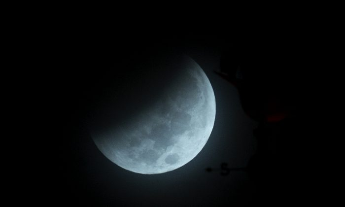 The Earth's shadow begins to fall on the moon during a total lunar eclipse, as seen above Miami, Wednesday, Oct. 8, 2014. (AP Photo/Wilfredo Lee)