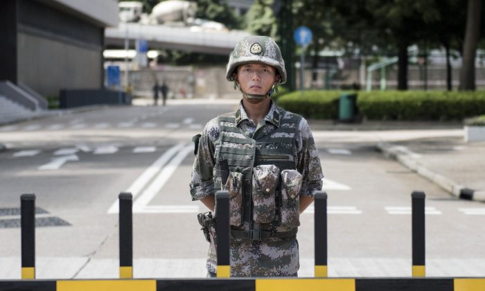A Chinese People's Liberation Army (PLA) soldier stands guard at the entrance to the PLA's Hong Kong garrison headquarters in Hong Kong on Aug. 29, 2014. Hong Kong's Chengming magazine claims that at a Sept. 15 meeting high-ranking Chinese Communist Party official Zhang Dejiang sketched the conditions under which martial law would be imposed on the restive city of Hong Kong. (Alex Ogle/AFP/Getty Images)