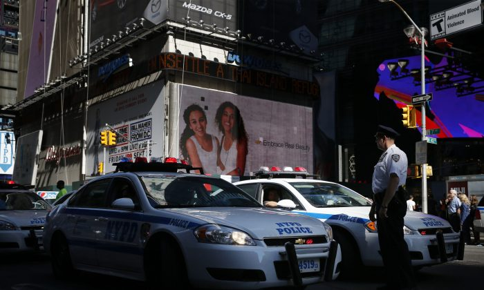 A police officer helps to park police cars in Times Square in New York on Sept. 17, 2014. Two police officers from New York have been charged with sexually assaulting a woman in an Atlantic City casino. (AP Photo/Seth Wenig)