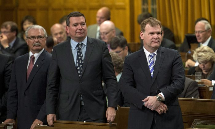 Foreign Affairs Minister John Baird rises in the House of Commons along with Ministers Christian Paradis and Gerry Ritz to vote for an air combat mission against ISIL on Oct. 7. The NDP and Liberals voted against the motion, which cleared the way for Canadian CF-18s to take part in airstrikes in the Middle East. (The Canadian Press/Justin Tang)