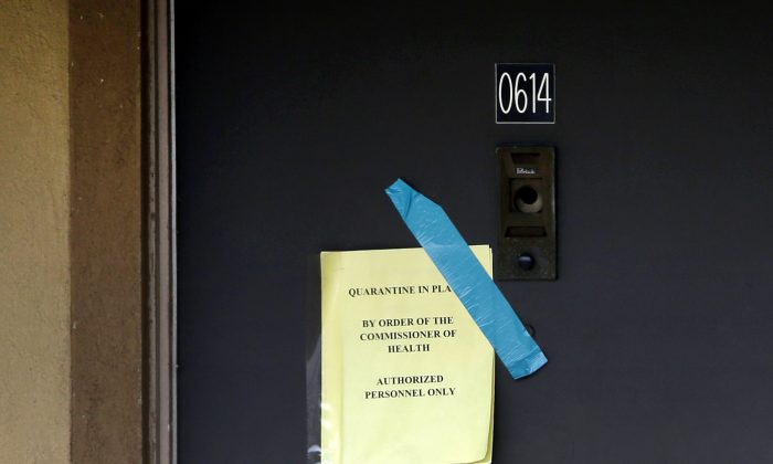A sign on the door of the apartment where Thomas Eric Duncan stayed with family warns that the unit has been quarantined by the commissioner of health, Wednesday, Oct. 8, 2014, in Dallas. Texas Health Presbyterian Hospital Dallas, where Duncan was being treated for Ebola, said that Duncan has died. The apartment was stripped bare, including the blinds that used to hang in the winds. (AP Photo/Tony Gutierrez)