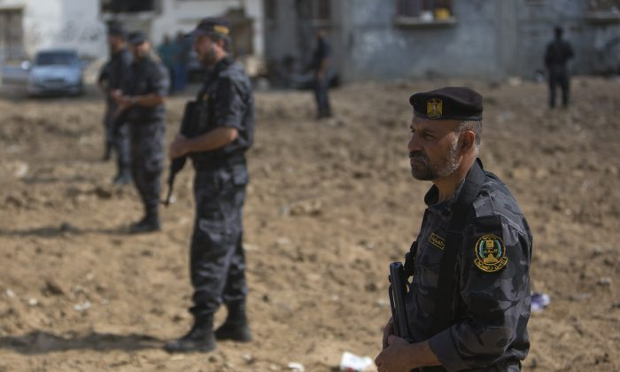 Palestinian Hamas security officers stand guard during the visit of Palestinian Prime Minister Rami Hamdallah to Gaza's neighborhood of Shijaeyih, Thursday, Oct. 9, 2014. Members of the new Palestinian unity government assembled in Gaza on Thursday for their first Cabinet session in the war-battered territory - a largely symbolic meeting meant to mark the end of absolute Hamas control of the coastal strip. (AP Photo/Khalil Hamra)