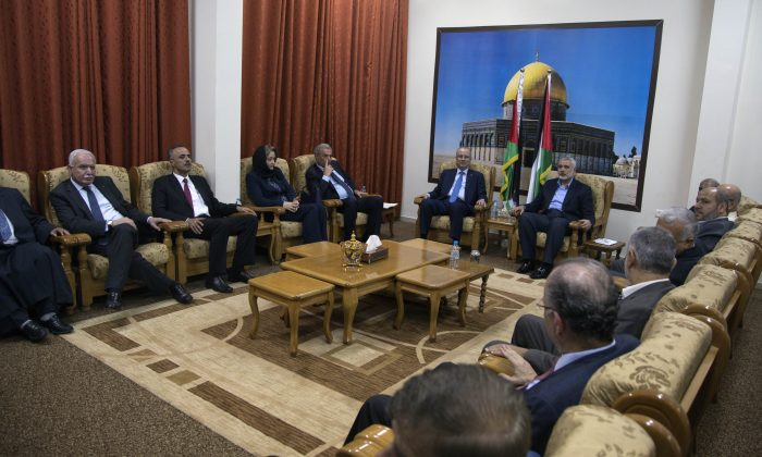 Palestinian Prime Minister Rami Hamdallah and the ministers of the the new Palestinian unity government meet with top Hamas leader in Gaza, Ismail Hamiyeh, in Gaza City, Thursday, Oct. 9, 2014. Members of the new Palestinian unity government assembled in Gaza on Thursday for their first Cabinet session in the war-battered territory,  a largely symbolic meeting meant to mark the end of absolute Hamas control of the coastal strip. (AP Photo/Khalil Hamra)