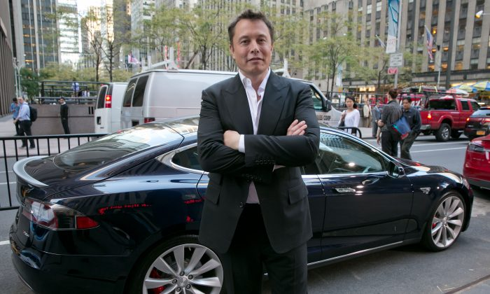 SpaceX billionaire founder and chief executive, and Tesla Motors CEO Elon Musk, poses beside a Tesla in New York on Sept. 17, 2014. (AP Photo/Richard Drew)