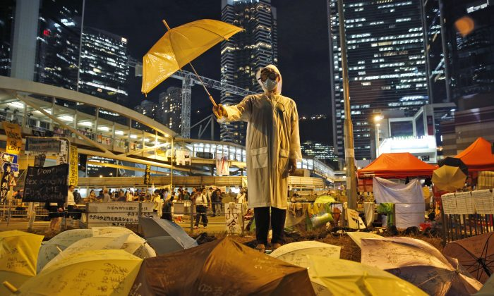 A protester holds an umbrella during a performance on a main road in the occupied areas outside government headquarters in Hong Kong's Admiralty in Hong Kong Thursday, Oct. 9, 2014.  (AP Photo/Kin Cheung)