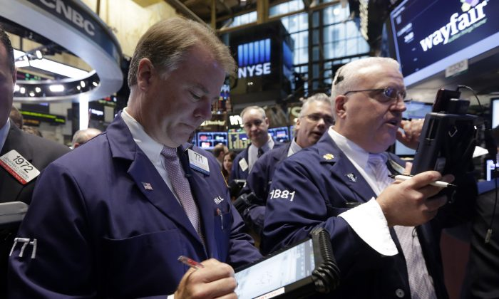 Traders F. Hill Creekmore and Thomas Ferrigno (R) work on the floor of the New York Stock Exchange, Thursday, Oct. 2, 2014. US stocks were solidly lower in early trading Thursday, Oct. 9, 2014, pruning back some of the gains from a massive rally the day before. Gap shares plunged after the company announced its CEO was retiring. (AP Photo/Richard Drew)