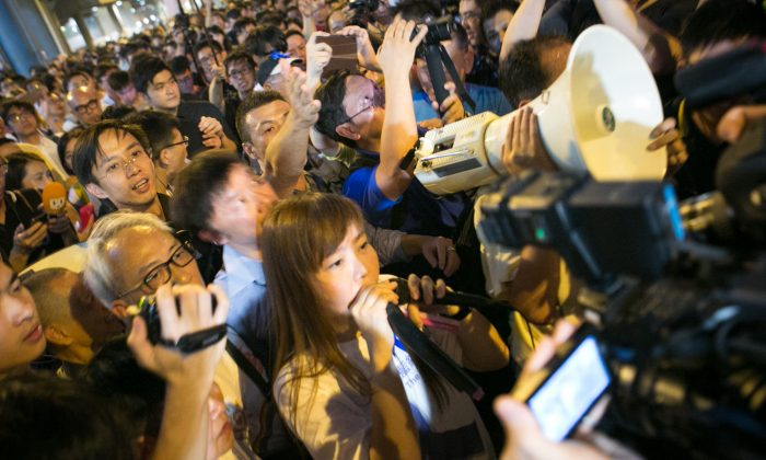 A woman who is pro-CCP speaks on a loud speaker as pro-democracy protesters boo and yell at her in the Central District of Hong Kong on Oct. 7. (Benjamin Chasteen/Epoch Times)