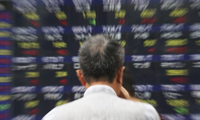 A man watches an electronic stock board of a securities firm in Tokyo, Thursday, Sept. 25, 2014. US stocks were solidly lower in early trading Thursday, Oct. 9, 2014, pruning back some of the gains from a massive rally the day before. Gap shares plunged after the company announced its CEO was retiring. (AP Photo/Mark Lennihan)