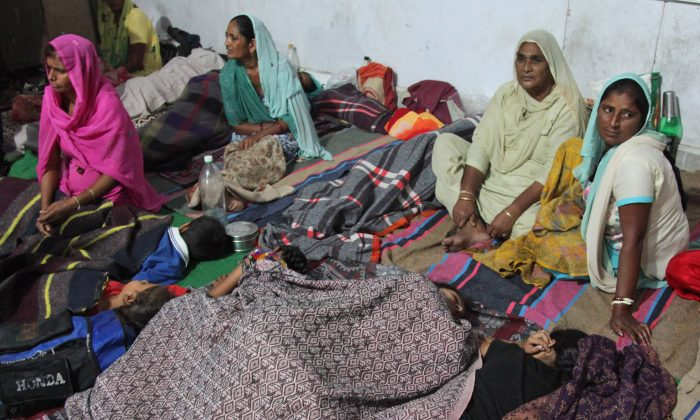 In this Thrusday, Oct. 9, 2014 photo, Indian women take shelter at Abdullian village, in Jammu and Kashmir state, India. A fierce trading of mortar shells and gunfire between India and Pakistan began Sunday night, marking the most serious violation of a 2003 cease-fire accord. (AP Photo/Channi Anand)