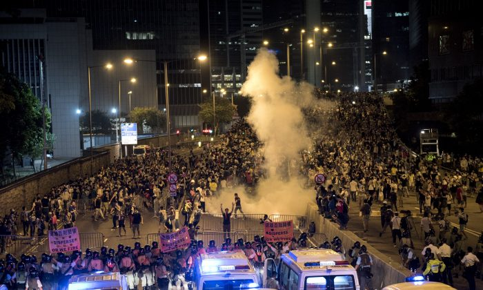 Police fire tear gas at pro-democracy protesters in Hong Kong on Sept. 28, 2014. On Sept. 29, Voice of America put into effect a previously scheduled cut in TV broadcasts to Hong Kong and China, broadcasts that were replaced by Radio Free Asia programming. (Alex Ogle/AFP/Getty Images)